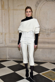 Olivia Palermo sported a multilayered look, consisting of a cropped boatneck sweater, a lace-up tube top, and a turtleneck--all by Dior--during the label's Haute Couture show.