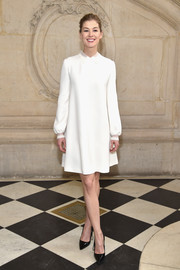 Rosamund Pike was all about simple elegance in a collared white shift dress at the Dior fashion show.