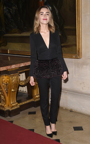 Kiernan Shipka looked sharp in her black Dior Couture ensemble, consiting of a deep-V peplum top and matching pants, during the label's Cruise show.