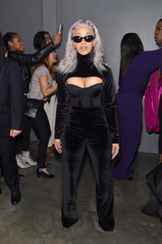 Cardi B looked provocative in a black shrug sweater teamed with a corset at the Christian Siriano fashion show.