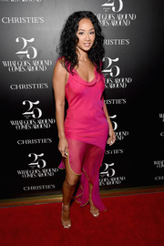 Draya Michele attended the Christie's x What Goes Around Comes Around 25th anniversary auction preview wearing a slinky fuchsia dress with a cowl neck and an asymmetrical hem.