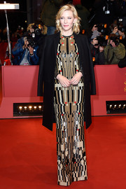Cate Blanchett arrived for the BIFF premiere of 'Cinderella' wearing a classic black coat over a patterned column dress.