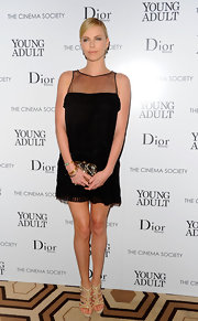 Charlize Theron added shine to her simply chic red carpet look with a detailed gold hard case clutch.