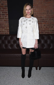 Kate Bosworth contrasted her feminine coat with edgy black over-the-knee boots by Stuart Weitzman.