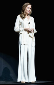 Angelina Jolie chose a Juan Carlos Obando ensemble, consisting of white wide-leg pants and a tie-neck blouse, for her appearance at CinemaCon.