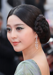 Fan Bingbing wore her hair in sleek center part braids at the Cannes Film Festival. dangling diamond earrings completed her look.