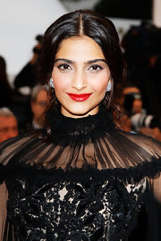 Sonam Kapoor contrasted her dark outfit with bright red lipstick at the Cannes Film Festival closing ceremony.