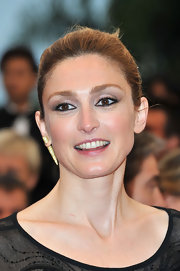 Clotilde Courau applied soft neutral shadows along with rich black liner and mascara to create her eye-enhancing look.