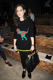 Winona Ryder kept it fun and youthful in a dinosaur sweater by Coach while attending the label's fashion show.