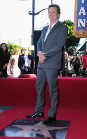 Colin looks dapper as ever in a slim fitting gray suit with subtle pinstripes.