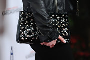 Kelly showed off her patent leather studded clutch while hitting the red carpet.