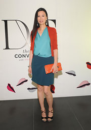 Wendi Deng attended an event by DVF wearing pastel shades of green (top and skirt) and an orange cardigan.