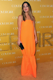 Drew Barrymore paired her vibrant citrus hued dress with a black Cavallino roll clutch.
