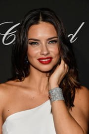Adriana Lima styled her white dress with a chic silver cuff.