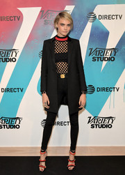 Cara Delevingne coordinated her outfit with a pair of red and black triple-strap heels.