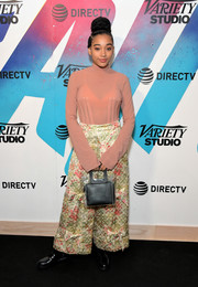 Amandla Stenberg jazzed up her simple top with a pair of flared floral trousers by Simone Rocha.