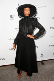 Halima Aden paired her blouse with a black maxi skirt.