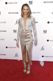 Candice Swanepoel looked fierce in a metallic column dress with a plunging neckline, slashed sides, and a high front slit at the 2019 Fashion Los Angeles Awards.
