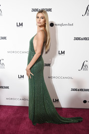 Hailey Baldwin got glam in a beaded emerald gown by Tommy Hilfiger for the 2018 Fashion Media Awards.