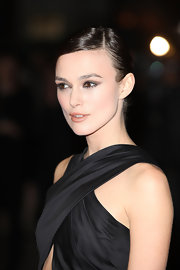 Keira Knightly's look can be quickly recreated by using using two eyeshadow pencils. We love Urban Decay 24/7 Glide-On Shadow Pencils in Midnight Cowboy and Barracuda. First sweep on the lighter shade all over entire upper lids and blend with fingertips. Then use the dark shade to create a heavy line along the upper lash lines going slightly past the outer corners and lightly smudge with fingertips. For more intensity, use a black eye pencil to line the inner rims of eyes and coat lashes with a volumizing mascara.