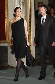 Princess Mary looked sophisticated in the chic black one shoulder dress she wore. Classic black pumps and stunning gold jewelry complete her look.