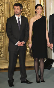 Princess Mary wore an armful of gold beaded bracelets to complement her elegant one shoulder dress.