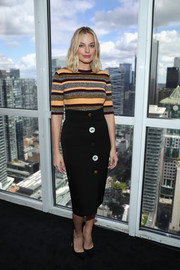 A black Ji Oh pencil skirt adorned with oversized buttons finished off Margot Robbie's outfit.