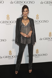 Bella Hadid looked disco-ready at the De Grisogono party in a Givenchy pantsuit rendered in metallic stripes.