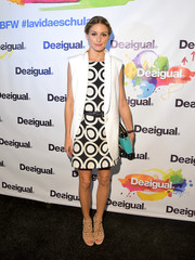 Olivia Palermo layered a white tux-style vest over a mod mini for the Desigual fashion show.