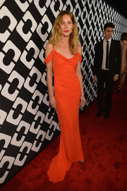 Erin Wasson looked sultry in a draped orange evening dress at the Journey of a Dress exhibition opening.