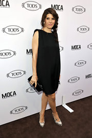 Marisa wears a little black shift dress with snake print shoes. Her side braid is darling!