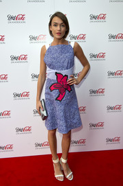 Ella Catliff balanced out her vibrant dress with minimalist white ankle-cuff sandals.