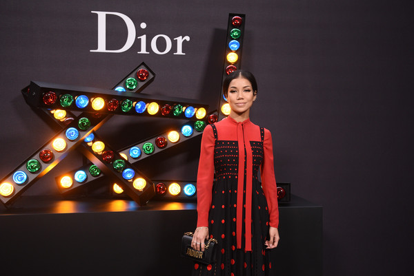 Jhene Aiko teamed a black leather clutch with a polka-dot dress for the Dior Homme Fall 2018 show.