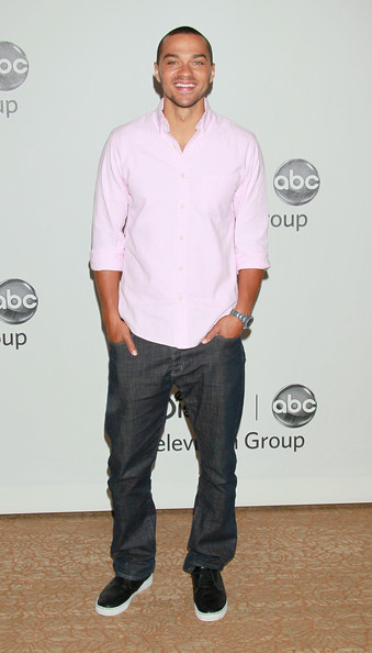 Jesse Williams wore sporty black and white sneakers with a polished button down and dark denim jeans.