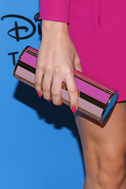 Christa accessorized her look with a pink striped cylindrical clutch.
