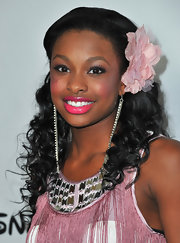 Coco Jones stayed in touch with her feminine side by choosing to top her hairdo with an oversized flower shaped fascinator.