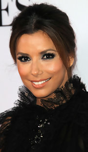 Eva Longoria's bright eyes sparkled at the 'Desperate Housewives' final season kick-off party. To try her flirty look, first line top and bottom lash lines with a dark eye pencil. Use lash glue to attach false lash strips to upper lash lines and finish with a generous coat of mascara.
