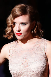 Scarlett Johansson wore her hair in a retro style to the Dolce & Gabbana Spring 2012 fashion show. To the non-professional, her Marcel waves are a bit tricking to recreate. An easier option is to set mid-length hair on hot rollers. After removing the rollers,  relax the curls slightly by brush tresses with a natural bristle brush, then make a deep side part. Smooth the hair on the top of the head, tousle ends lightly and spritz with a medium-hold hairspray.