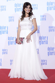 Penelope Cruz paired her dress with a metallic silver clutch by Chanel.