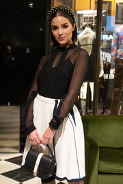 Olivia Culpo attended the 'Double Exposure' book signing carrying a black-and-white leather purse by Valextra.