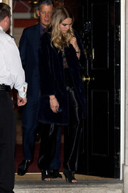 Cara Delevingne wore her coat with a pair of black silk pants and a lace top.