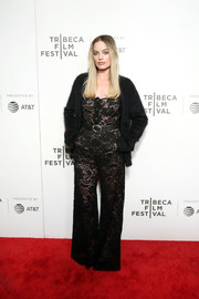 Margot Robbie added a cozy touch with a black cardigan.