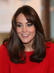 Kate Middleton wore her hair with a bouncy undercurl and side-swept bangs while attending the Anna Freud Centre Christmas party.