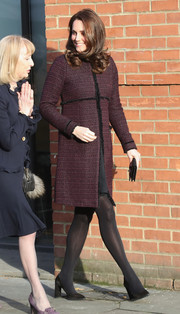 Kate Middleton stayed warm in a burgundy tweed maternity coat by Seraphine at the Magic Mums Christmas party.