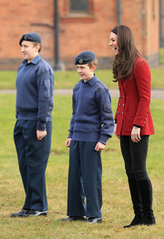 Kate Middleton completed her outfit with black knee-high boots by Stuart Weitzman.