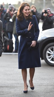 Kate Middleton stayed warm in classic style with a navy wool coat by Hobbs for her visit to the Reach Academy Feltham.