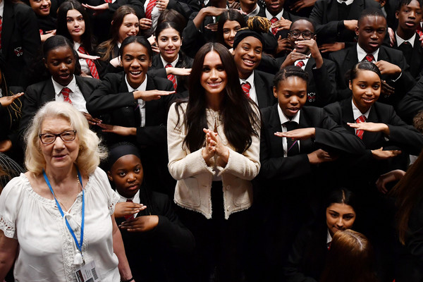 More Pics of Meghan Markle High-Waisted Pants (3 of 30) - Pants & Shorts Lookbook - StyleBistro [image,people,crowd,event,audience,photography,gesture,performance,smile,choir,student,school children,meghan,crop,sign,dagenham,duchess of sussex visits the robert clack upper school,robert clack school,school assembly,visit,crowd]