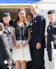 Prince William and Kate Middleton continued their world tour with a trip to LA. Kate wore a Whistles crochet top with a white pleated skirt by the same brand, completing her look with a pair of Prada navy pumps. The Duchess wore her hair half down in soft waves for this chic day look.
