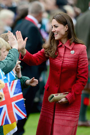 Kate Middleton matched a nude tube clutch with a luxurious red coat for her tour of Scotland.