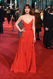 Dakota Johnson donned a dangerously low-cut ruffle gown by Dior for the BAFTAs.
